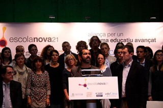 Pla mig obert del director d'Escola Nova 21, Eduard Vallory, intervenint en un faristol a la presentació del projecte, amb una vintena de directors de centres a darrera i el logotip al fons, el 21 d'abril del 2016. (Horitzontal)